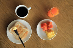 Breakfast set, toast with butter, fresh fruit, coffee, orange juice. Stock Photos