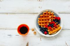 Breakfast set with waffles. Breakfast set. Warm homemade traditional belgian waffles with fresh berry and cup of espresso on white rustic wooden background. Flat Royalty Free Stock Images
