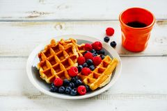 Breakfast set with waffles. Close up of breakfast set. Warm homemade traditional belgian waffles with fresh berry and cup of espresso on white rustic wooden Royalty Free Stock Image