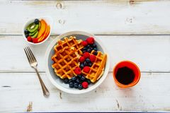 Breakfast set with waffles. Flat-lay of breakfast set. Warm homemade traditional belgian waffles with fresh berry and cup of espresso on white rustic wooden Royalty Free Stock Photo