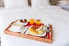 Breakfast set  in wooden tray serving on bed Royalty Free Stock Images