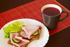 Breakfast setting with cup of tea. Toast with ham and vegetables Stock Photography