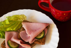 Breakfast setting with cup of tea. Toast with ham and vegetables Royalty Free Stock Photos