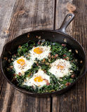 Breakfast Skillet of Eggs and Greens. And rustic table Royalty Free Stock Images