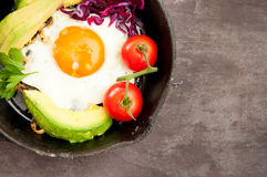 Breakfast skillet. Pan of fried egg, avocado and tomato. Served on a gray stone slate background Stock Photos