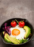 Breakfast skillet. Pan of fried egg, avocado and tomato. Served on a gray stone slate background Royalty Free Stock Image
