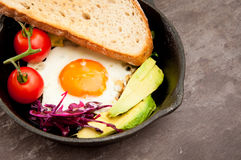 Breakfast skillet pan. Of fried egg, avocado and tomato. Served on a gray stone slate background Stock Images