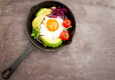 Breakfast skillet. Pan of fried egg, avocado and tomato. Served on a gray stone slate background Royalty Free Stock Photography
