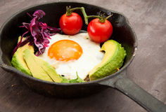 Breakfast skillet. Pan of fried egg, avocado and tomato. Served on a gray stone slate background Stock Image