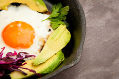 Breakfast skillet. Pan of fried egg, avocado and tomato. Served on a gray stone slate background Stock Photography