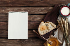 Breakfast. A slice of bread, honey, milk and wheat ears on an ol. D wooden background with a notepad. View from above. Rustic style. Wooden background. copy Royalty Free Stock Image
