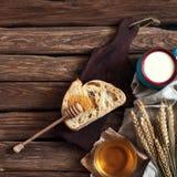 Breakfast. A slice of bread, honey, milk and wheat ears Royalty Free Stock Photo