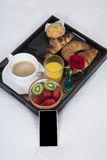 Breakfast and smartphone on bed Royalty Free Stock Image