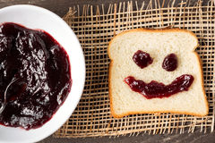 Breakfast smiley shaped bread with cherry jam Stock Photography