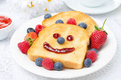 Breakfast with a smiling toast, fresh berries, berry jam Stock Images