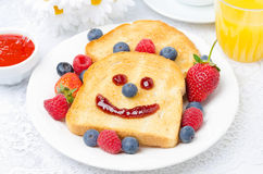 Breakfast with a smiling toast, fresh berries, berry jam Stock Photos
