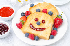 Breakfast with a smiling toast, fresh berries, jams. Horizontal Royalty Free Stock Photography