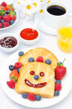 Breakfast with a smiling toast, fresh berries, jams, juice, coffee. Breakfast with a smiling toast, fresh berries, jams, juice and black coffee, top view Stock Photography