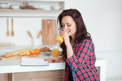 Breakfast - Smiling woman reading book in white kitchen, fresh orange juice Royalty Free Stock Photography