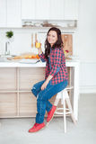 Breakfast - Smiling woman reading book in white kitchen, fresh orange juice Stock Image