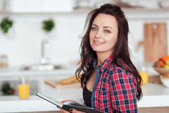 Breakfast - Smiling woman reading book in white kitchen, fresh orange juice Royalty Free Stock Photos