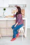 Breakfast - Smiling woman reading book in white kitchen, fresh orange juice Royalty Free Stock Photo