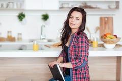Breakfast - Smiling woman reading book in white kitchen, fresh orange juice Stock Images