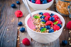 Breakfast smoothie bowl  with granola, fresh raspberry, blueberry, chia seeds and mint. Breakfast smoothie bowl  with granola, fresh raspberries, blueberries Stock Images