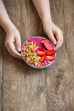 Breakfast smoothie bowl in hands. Eating healthy breakfast bowl. Acai smoothie, granola, seeds, fresh strawberries in ceramic bowl in female child hands over Royalty Free Stock Image