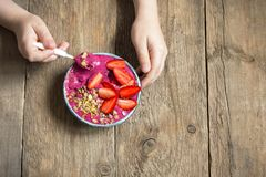 Breakfast smoothie bowl in hands. Eating healthy breakfast bowl. Acai smoothie, granola, seeds, fresh strawberries in ceramic bowl in female child hands over Royalty Free Stock Photos