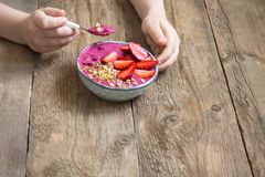 Breakfast smoothie bowl in hands. Eating healthy breakfast bowl. Acai smoothie, granola, seeds, fresh strawberries in ceramic bowl in female child hands over Stock Photos