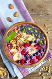 Breakfast smoothie bowl. Healthy breakfast smoothie bowl topped with fruits, nuts, berries and seeds over rustic wooden background with copy space Stock Image