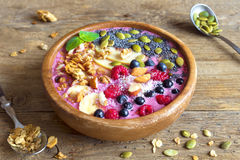Breakfast smoothie bowl. Healthy breakfast smoothie bowl topped with fruits, nuts, berries and seeds over rustic wooden background with copy space Royalty Free Stock Photo