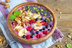 Breakfast smoothie bowl. Healthy breakfast smoothie bowl topped with fruits, nuts, berries and seeds over rustic wooden background with copy space Royalty Free Stock Image