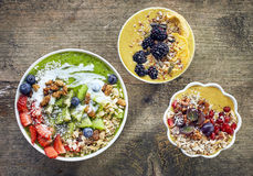 Breakfast smoothie bowls. Various breakfast smoothie bowls on wooden table, top view Royalty Free Stock Photos