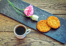 Breakfast or snack – cup of freshly brewed coffee, sesame cookies, pink lisianthus  flower Royalty Free Stock Photography