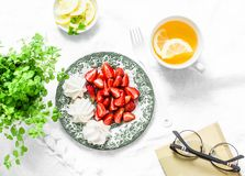 Breakfast or snack table - fresh strawberries, meringue, green tea with lemon. Cozy home still life on a light background royalty free stock photography