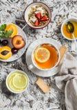 Breakfast or snack table. Lemon tea, fresh fruit, yogurt with granola, biscuits Stock Image