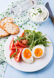 Breakfast with soft-boiled egg, arugula and tomatoes Royalty Free Stock Images