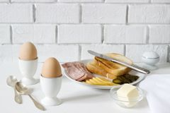 Breakfast with soft-boiled egg, bread toast, ham, cheese and canned cucumbers. Rustic style. Stock Image