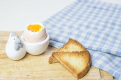 Breakfast soft boiled egg and toast. Next to a blue checked napkin Stock Photography