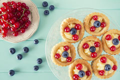 Breakfast. Some vol-au-vent with blueberries and red currants on a cake stand over a robin egg blue wooden table. Vintage Style Stock Images