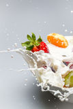 Breakfast splash with milk and fresh fruits Stock Images