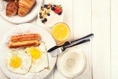 Breakfast of sunny side up eggs, sausages, orange juice, and fru Stock Image