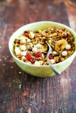 Breakfast super bowl with granola or muesli with oat flakes, banana chips, dried cherry, hazelnuts and white chocolate on a wooden. Table, selective focus royalty free stock photos