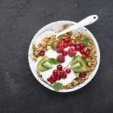 Breakfast super bowl homemade baked granola with yoghurt, kiwi slices, currant, mint, basil and fresh flower honey. Top royalty free stock photos