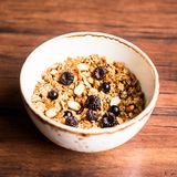 Breakfast super bowl of homemade granola or muesli with oat flakes, black currant, black raspberry and peanuts on a wooden table,. Selective focus. Served with stock photo