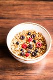 Breakfast super bowl of homemade granola or muesli with oat flakes, black currant, black raspberry and peanuts on a wooden table,. Selective focus. Served with royalty free stock images