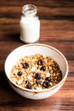 Breakfast super bowl of homemade granola or muesli with oat flakes, black currant, black raspberry and peanuts on a wooden table,. Selective focus. Served with royalty free stock photos