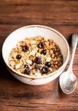 Breakfast super bowl of homemade granola or muesli with oat flakes, black currant, black raspberry and peanuts on a wooden table,. Selective focus. Served with royalty free stock image